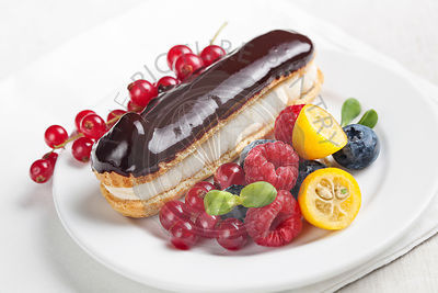 Chocolate eclair with berries on white plate