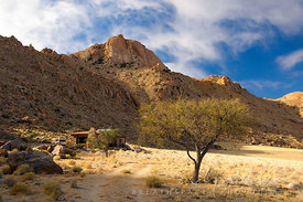 A stone cabin, with a SUV vehicle parked outside, below a sandstone mountain in the desert