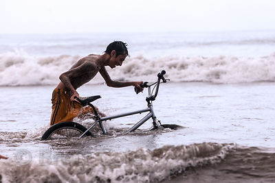 A man pushes a bicycle through the waters of the Arabian Sea in monsoon rains at Juhu Beach, Mumbai, India.