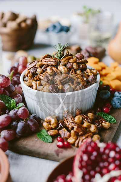 A bowl of spicy candied pecans are photographed from the front view as a part of a cheese and fruit board.