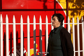 A woman walking past a white fence in front of a red wall in Santiago, Chile.
