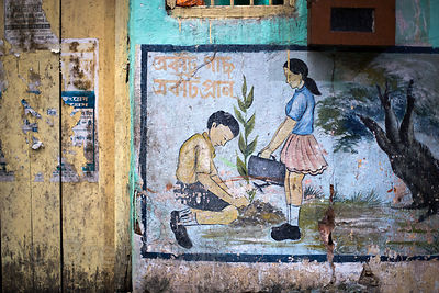 Weathered mural depicting a boy and girl watering a plant, Sovabazar, Kolkata, India