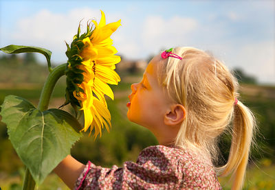 Girl smelling sunflower outdoors