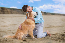 Man Hugging a Golden Retriever on a Beach