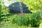 Lake with bottle dome beyond. Westonbury Mill Water Garden, Pembridge, Herefordshire, UK