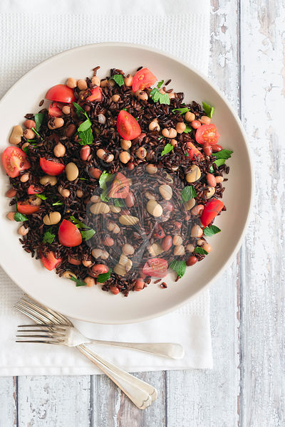 Bowl of black rice salad with forks.