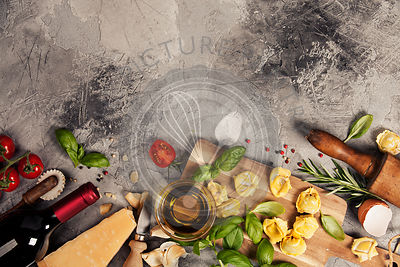 Italian food background with ravioli, vine tomatoes, basil, spaghetti, spinach, onion, parmesan, olive oil, garlic, peppercor...