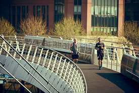 NEWCASTLE UPON TYNE, ENGLAND, UK - MAY 08, 2018: Two runners crossing the Millennium bridge on the morning sunlight.
