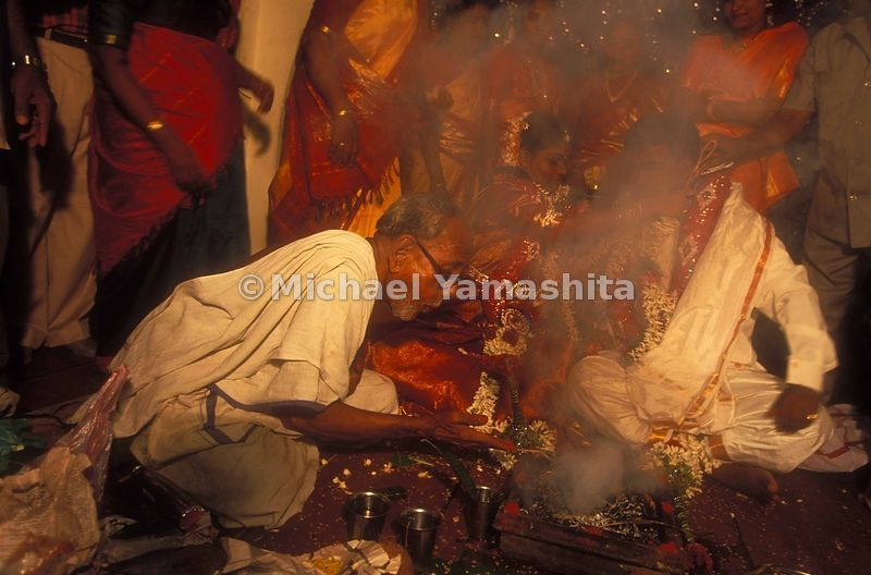 The priest throws rice grains onto the sacred fire, in keeoing with an ancient tradition.