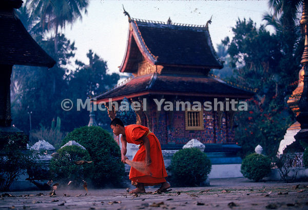 A monk sweeps the courtyard of Wat Xieng Thong as part of his morning ritual of chores in Luang Prabang, the old royal capita...