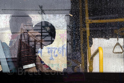 A man sleeps on a bus in monsoon rains, Alipore, Kolkata, India