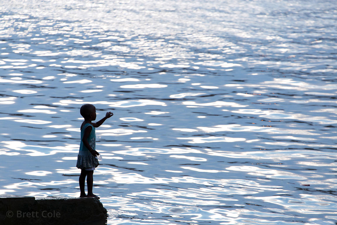 A girl stands near shimmering water on the Hooghly (Ganges) River, near Kumartoli Ghat, Kolkata, India