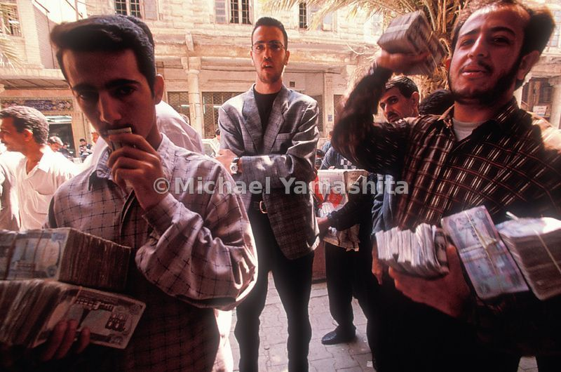 Weighed down with dinars, money changers stalk a Baghdad street where foreign journalists, merchants, and United Nations offi...