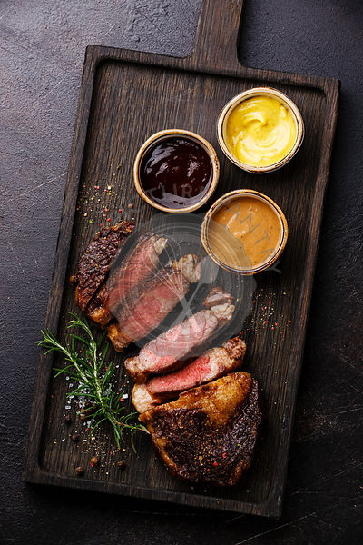 Sliced grilled Rib eye steak and three different sauces: Pepper sauce, Mustard and Barbecue on dark background