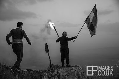 Kurdish Man On A Mountain Top Carrying A Burning Torch And A Kurdish Flag