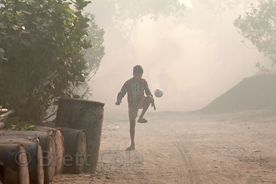 A boy dribbles a soccer ball on a dusty, polluted road in Dhapa, Kolkata, India. Dhapa is the site of Kolkata's largest landf...