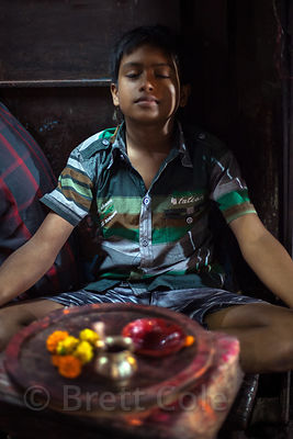 A boy meditates in a temple, Kalighat, Kolkata, India.
