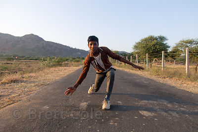 A man strikes a funny pose on a remote desert road, Kharekhari village, Rajasthan, India