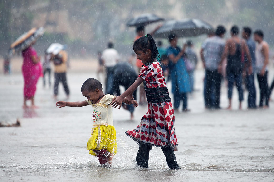 A girls walks her little sister through the water during monsoon rains at Juhu Beach, Mumbai, India.