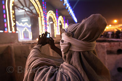 A Hindu pilgrim takes photos of the Kapil Muni temple on Sagar Island, India, during the Gangsagar Mela.