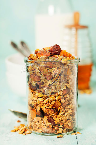 Homemade granola on rustic table. Healthy breakfast of oatmeal, muesli, nuts, seeds and dried fruit.