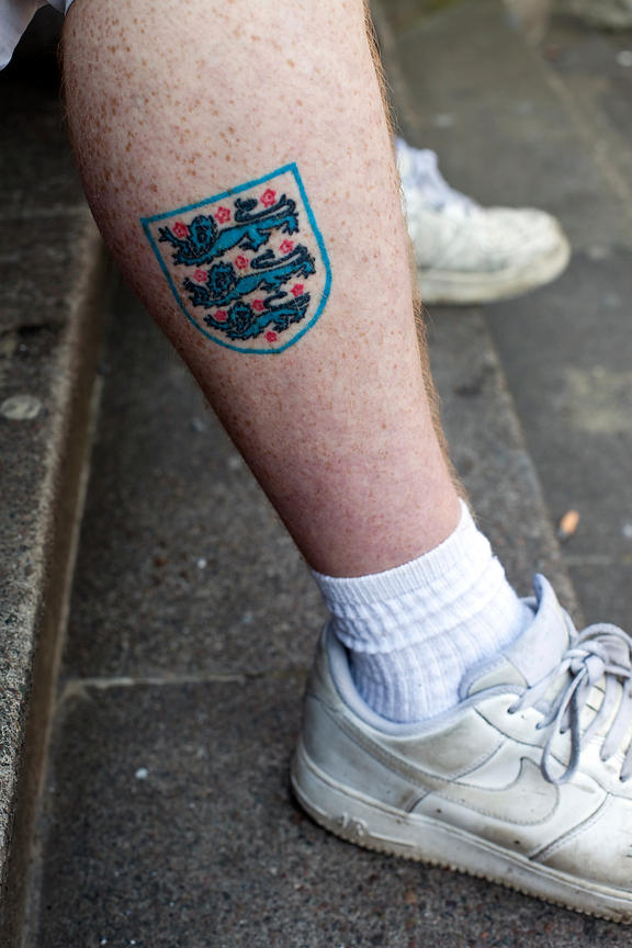 UK - London - A man with an England football tattoo on his leg. Hoxton Square