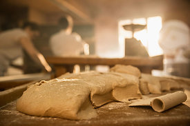 in an artisan bakery, close-up of bread dough. In the background the bakers work while the morning sun comes in through the w...