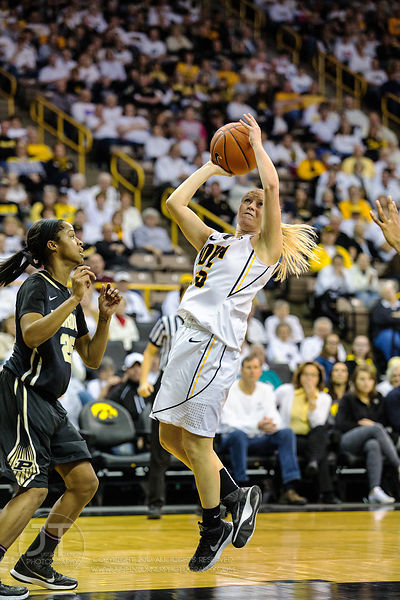 Iowa's Whitney Jennings (15) drives to the basket versus Purdue's April Wilson (25) during the second half of play at Carver-...