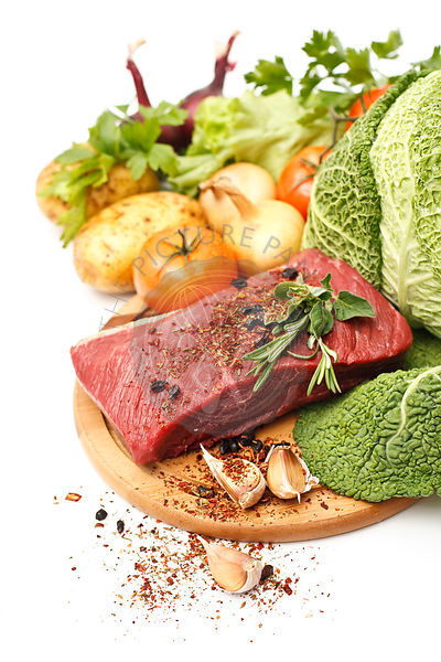 Raw meat on board with vegetables on white background