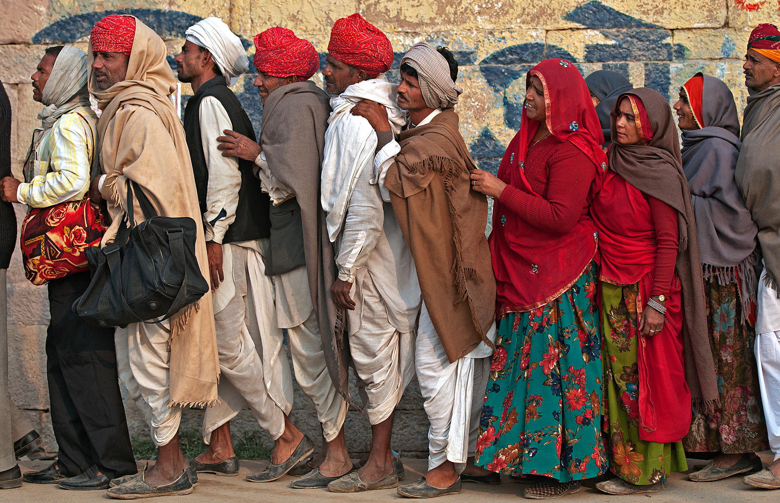 A group of Rajasthani women and men dressed in their traditional attire wait in the queue during the Kumbh Mela.