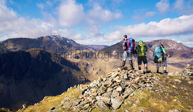 Three hikers looking out over the summits of High Crag, High Stile and Pillar from the summit of Fleetwith Pike, English Lake...