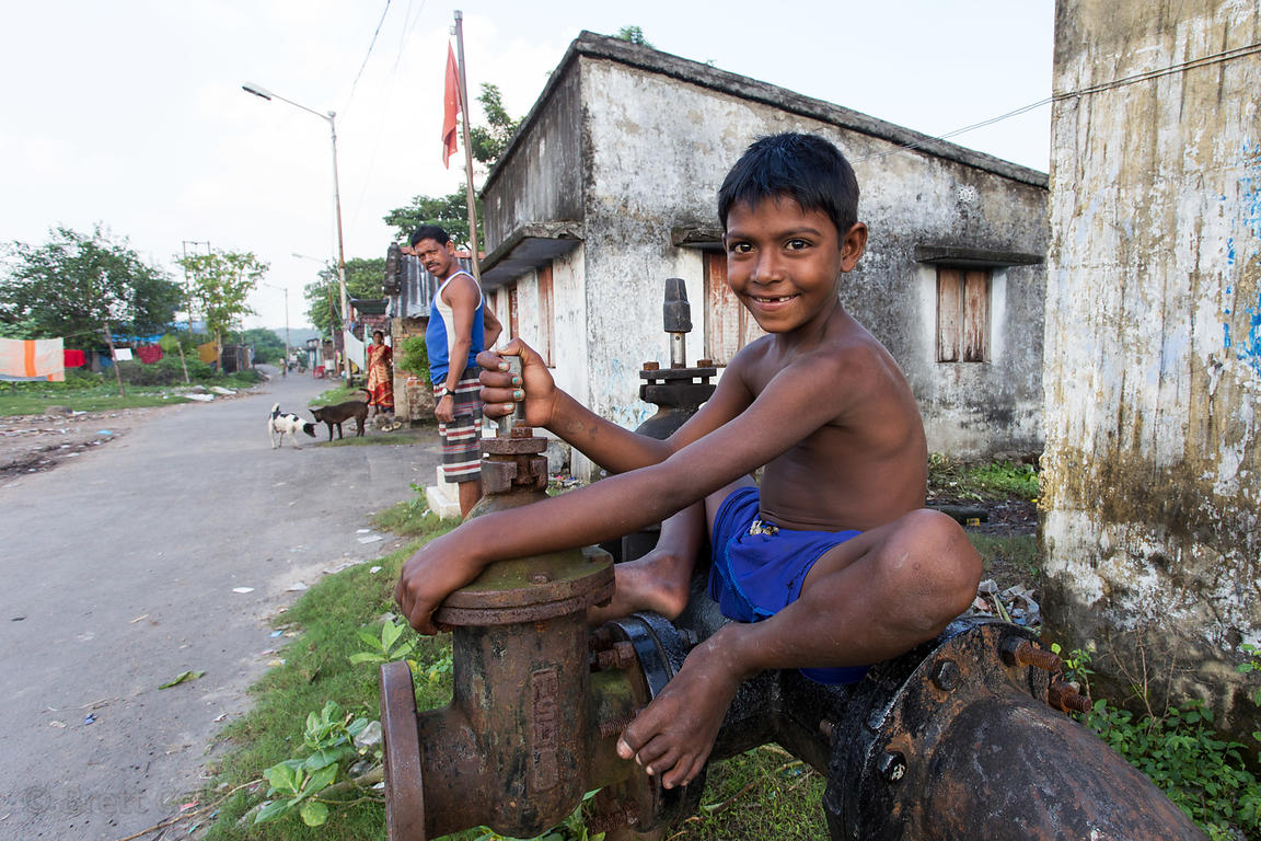 A boy plays with a water pump in Dhapa, Kolkata, India
