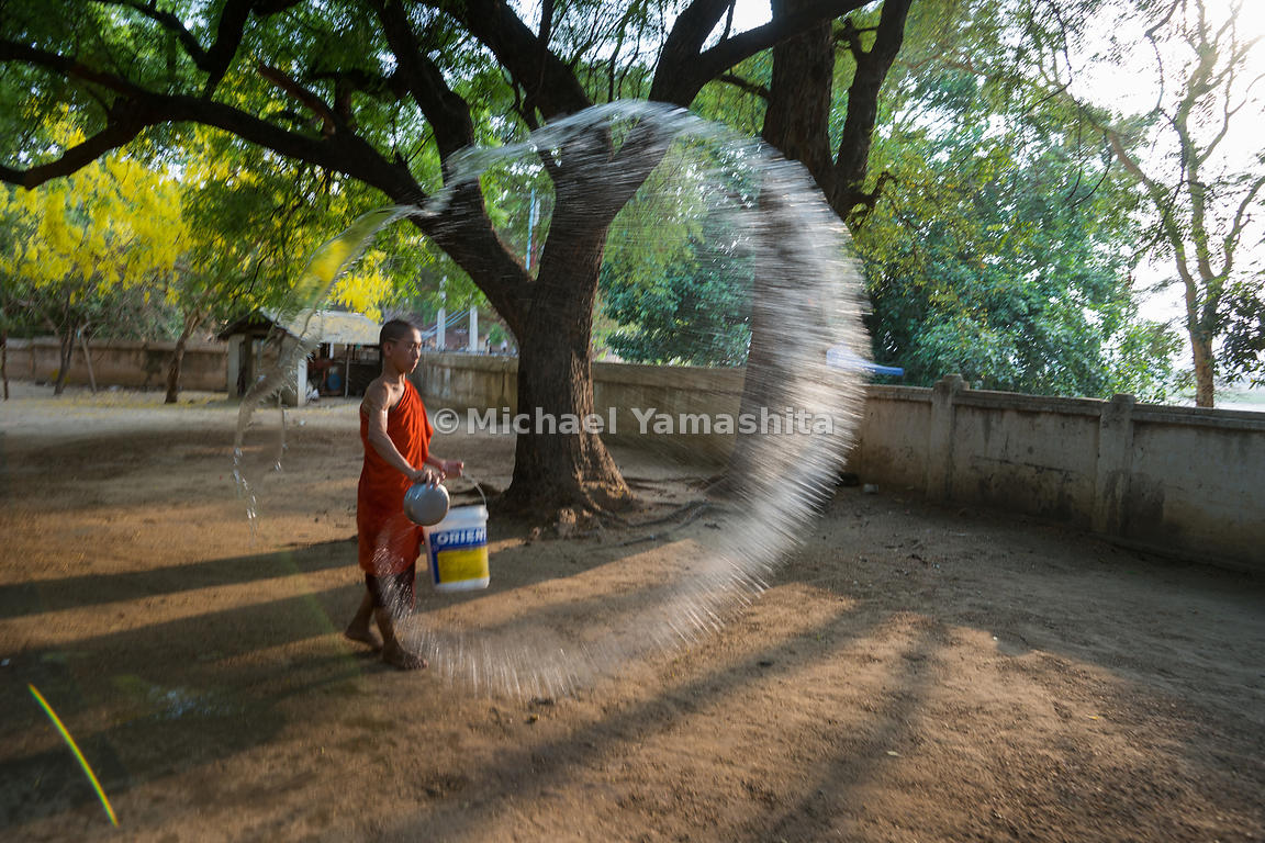 A monk sprays water over a dusty courtyard at Bagan's ancient Lawkananda Pagoda. Dampening the soil reduces the dust stirred ...