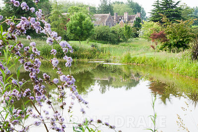 An informal garden of meadow, pond and specimen trees including conifers and birches, surrounds the formal garden defined wit...