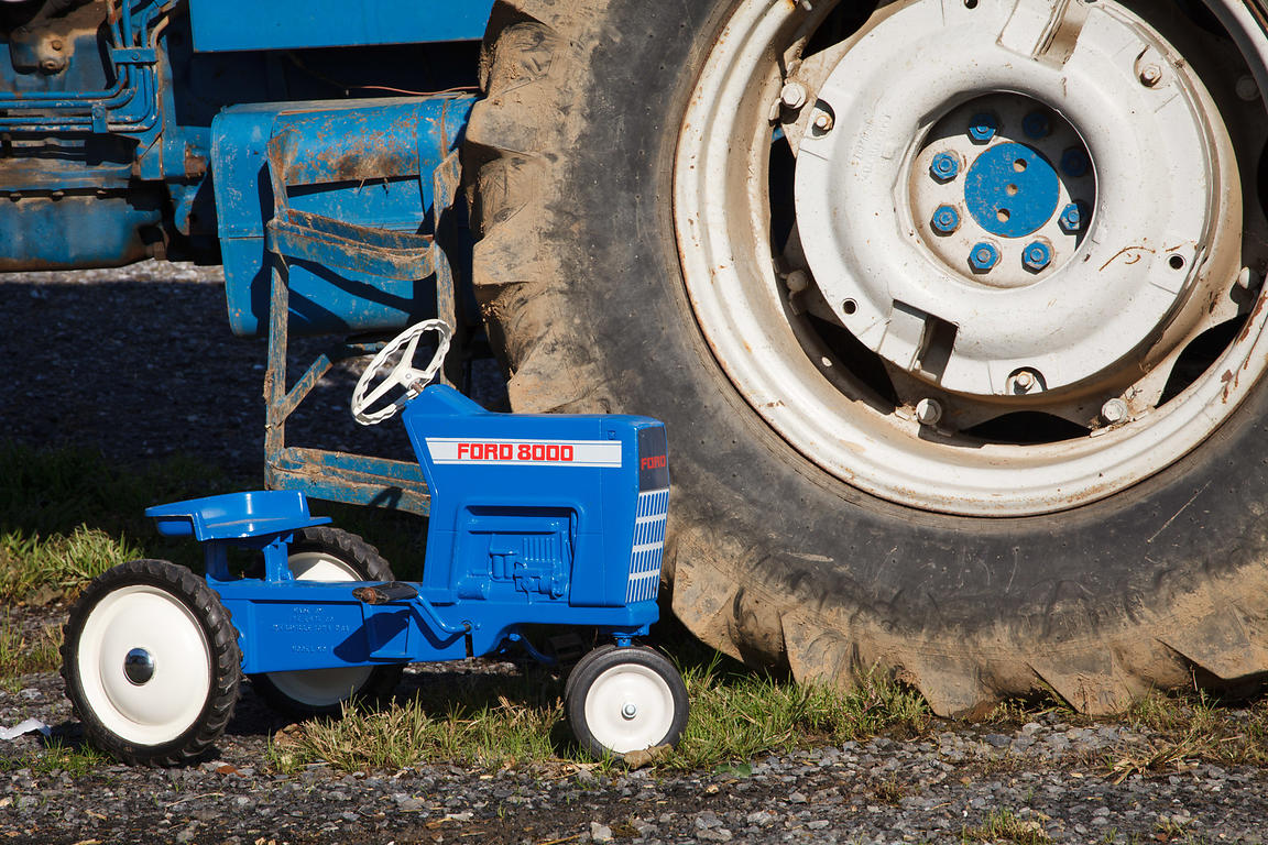 Note - not stage or arranged. A boy's blue toy Ford tractor next to his father's tractor,  Lancaster, Pennsylvania