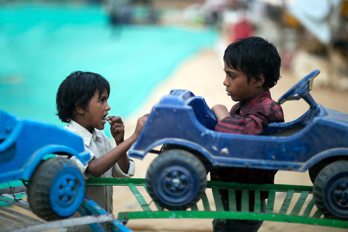 Two boys work at a carnival ride for small children during the Pushkar Camel Fair, Pushkar, Rajasthan, India