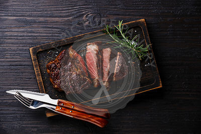 Sliced grilled meat barbecue steak Rib eye with knife and fork on burned black wooden background