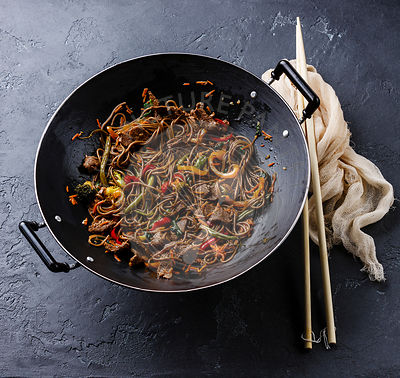 Stir fry noodles Yakisoba with beef and vegetables in wok pan on dark stone background