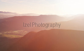 The warm sun of sunrise creeping over the ridge lines of the Derwent Fells and Newlands Beck in the English Lake District, UK.
