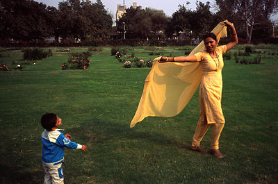 India - Delhi - A woman uses her sari to play with her child