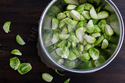 Quartered Brussels Sprouts in Bowl on Dark Wood Table