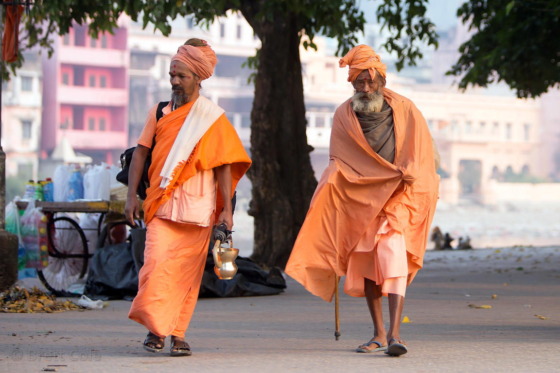 Two sadhus walk along the Ganges River in Haridwar, India