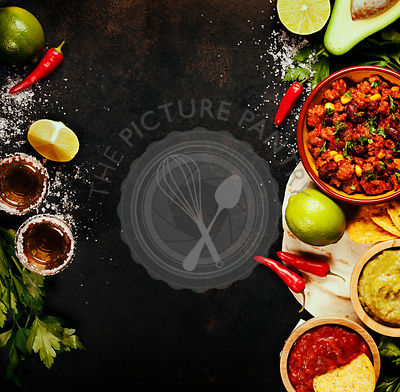 Mexican food concept: tortilla chips, guacamole, salsa, chilli with beans, tequila shots and fresh ingredients over vintage r...