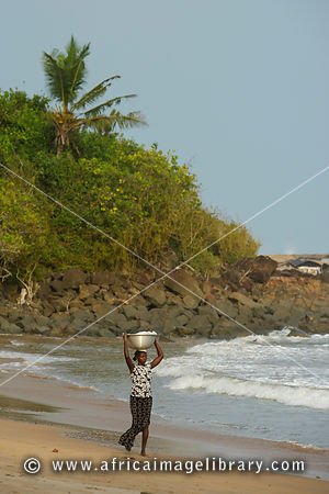 Woman walking on the beach, near Busua, Ghana