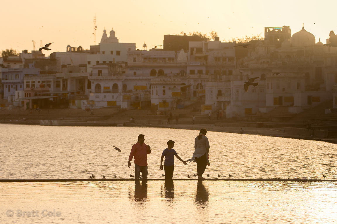 People visit shimmering golden Pushkar Lake, Pushkar, Rajasthan, India