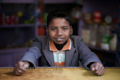 Portrait of a boy tending a market stall in Varanasi, India.