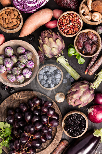 Assortment raw organic of purple ingredients: eggplants, artichokes, potatoes, onions, berries, nuts, carrots, brussel sprout...
