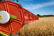 Close up of a Claas V900 35ft combine head with attached cameras, at work, harvesting barley. North Yorkshire, UK.