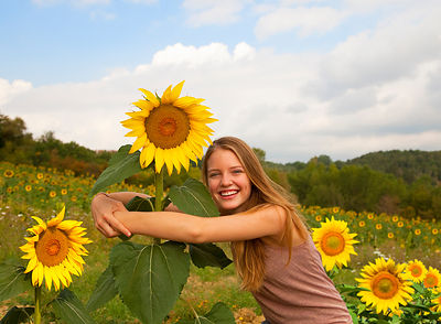 Teenage girl hugging sunflower in field