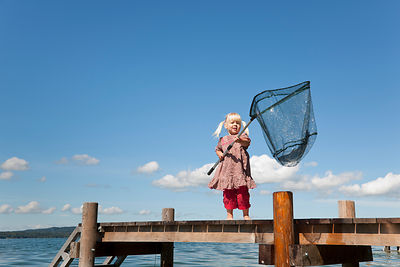 Girl fishing with net in lake